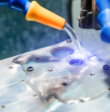 EDM CNC machine during operation. In the area of electro-fed coolant. Stock Photo