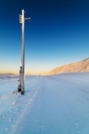 Winter road in the mountains. Inactive lighting column. Stock Photo