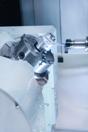 CNC milling machine during operation. Produce drill holes in the aluminium part.