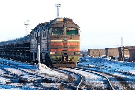 Diesel locomotive pulling freight train with bulk cargo. Polar tundra, winter.
