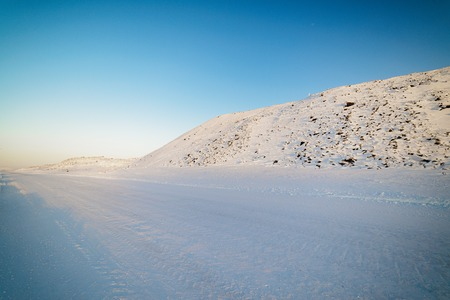 Winter road in snow-covered mountain slopes. Russian Far North.