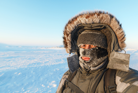 Portrait of a man with a face mask closed, his face covered with frost.