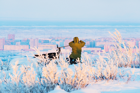 winter photos: Man with photo camera on tripod taking timelapse photos winter panorama of the city.. Poor lighting conditions. Stock Photo