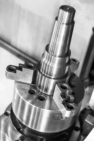 A metal workpiece clamped in the lathe chuck CNC machine. Shallow depth of field.