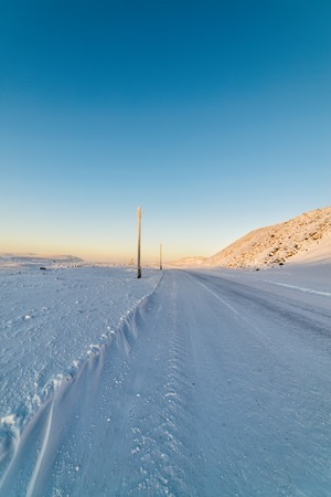telephone poles: Winter road, the snow-covered slopes. Older inactive light poles. Stock Photo