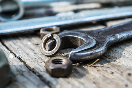 En superficie de madera vieja degradado se encuentran los antiguos, llaves aceitosas. Cerca dispersos viejas tuercas oxidadas. Foto de archivo