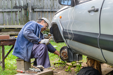 replaces: Senior mechanic replaces the vehicles front wheel. vehicle repair in the absence of the service station. Stock Photo