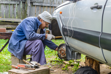 inconvenience: Senior mechanic repairing the front hub wheels. vehicle repair in the absence of the service station. Stock Photo
