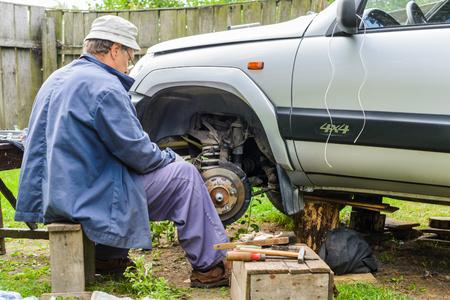 inconvenience: The mechanic is repairing the front hub wheels. car repair at home.
