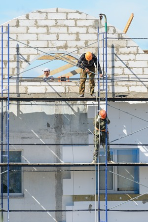 LYAKHOVICHI, BELARUS - AUGUST 28, 2016: Workers builders lift building materials on scaffolding Editorial