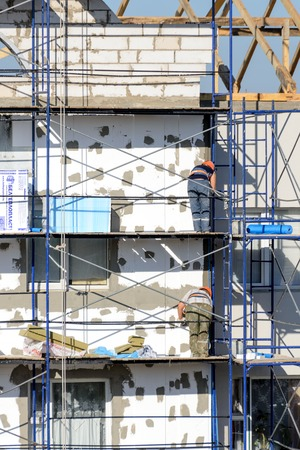 LYAKHOVICHI, BELARUS - AUGUST 28, 2016: Construction workers carry out work on plastering and insulation of external walls of the building