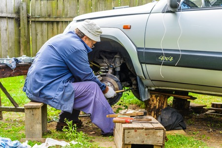 The mechanic is repairing the front suspension of the car at home. Car repair is a service station environment. Stock Photo