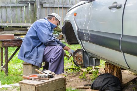 inconvenience: Senior mechanic repairing the front hub wheels. car repair at home.