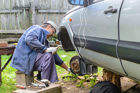 replaces: Senior mechanic replaces the vehicles front wheel. car repair garage in your home.