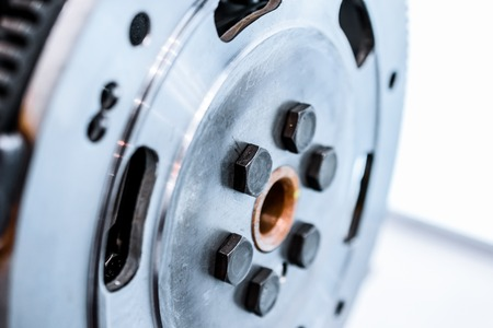 flywheel: Steel flywheel mounted on the engine. Abstract industrial background.