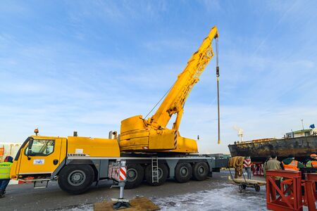 operative: MOSCOW, RUSSIA - NOVEMBER 11, 2016: State Unitary Enterprise Mosvodostok performs recovery vessels on coastal winter parking. Vehicle crane in the operative position, mounted on metal supports. Editorial