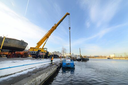 MOSCOW, RUSSIA - NOVEMBER 11, 2016: State Unitary Enterprise Mosvodostok performs recovery vessels on coastal winter parking. Powerful truck crane vessel begins to rise out of the water. Editorial