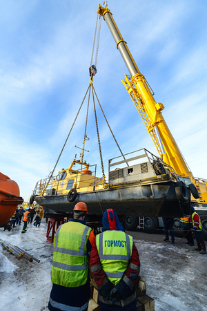 MOSCOW, RUSSIA - NOVEMBER 11, 2016: State Unitary Enterprise Mosvodostok performs recovery vessels on coastal winter parking. Workers control the installation of the ship.