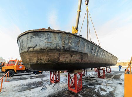 MOSCOW, RUSSIA - NOVEMBER 11, 2016: State Unitary Enterprise Mosvodostok performs recovery vessels on coastal winter parking. Barge mounted on abutments using a truck crane. Editorial