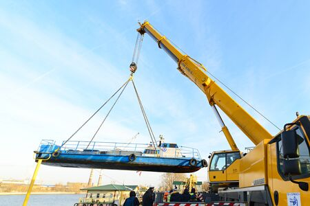 MOSCOW, RUSSIA - NOVEMBER 11, 2016: State Unitary Enterprise Mosvodostok performs recovery vessels on coastal winter parking. The ship rises transferred to shore with the help of truck crane. Editorial
