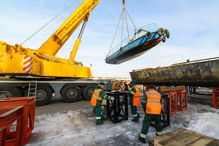 MOSCOW, RUSSIA - NOVEMBER 11, 2016: State Unitary Enterprise Mosvodostok performs recovery vessels on coastal winter parking. Workers prepare a place in the ship installation.