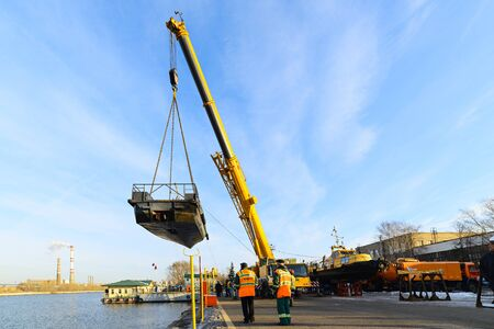 MOSCOW, RUSSIA - NOVEMBER 11, 2016: State Unitary Enterprise Mosvodostok performs recovery vessels on coastal winter parking. Car crane lifts the ship. Editorial