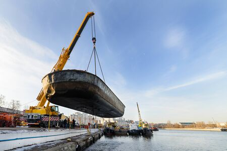 MOSCOW, RUSSIA - NOVEMBER 11, 2016: State Unitary Enterprise Mosvodostok performs recovery vessels on coastal winter parking. Car crane lifts the barge from Moscow river. Editorial