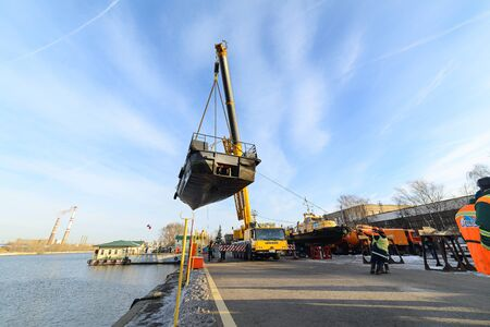 MOSCOW, RUSSIA - NOVEMBER 11, 2016: State Unitary Enterprise Mosvodostok performs recovery vessels on coastal winter parking. Truck crane moves the ship.
