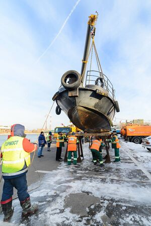 MOSCOW, RUSSIA - NOVEMBER 11, 2016: State Unitary Enterprise Mosvodostok performs recovery vessels on coastal winter parking. Installation work on the shores of the vessel. Editorial