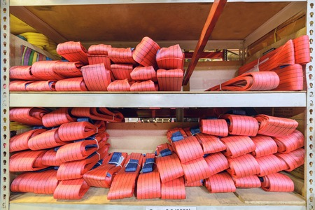 cable stitch: Red nylon soft lifting slings stacked in piles. Warehouse of finished products for industrial enterprises