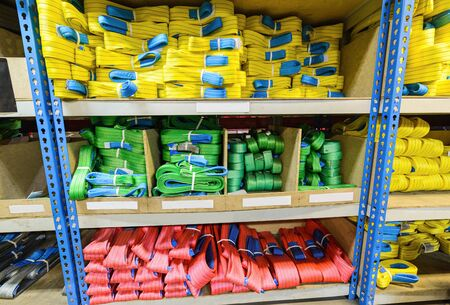 backstitch: Green, yellow and red nylon soft lifting slings stacked in piles. Warehouse of finished products for industrial enterprises Stock Photo