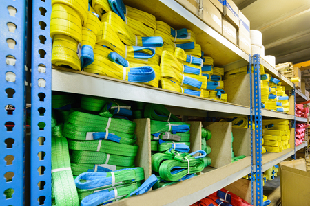 Green, yellow nylon soft lifting slings stacked in piles. Warehouse of finished products for industrial enterprises