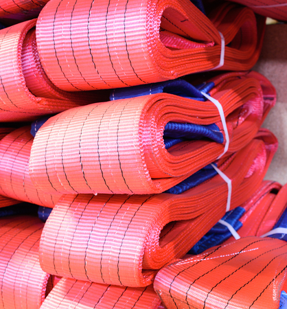 Red nylon soft lifting slings stacked in piles. Warehouse of finished products for industrial enterprises