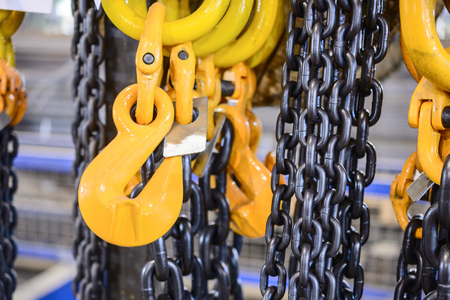 New chain cargo sling. Black steel chain and yellow cargo hooks. Abstract industrial background.