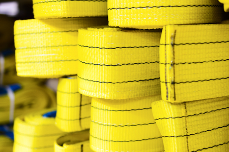 backstitch: Yellow nylon soft lifting slings stacked in piles. Warehouse of finished products for industrial enterprises