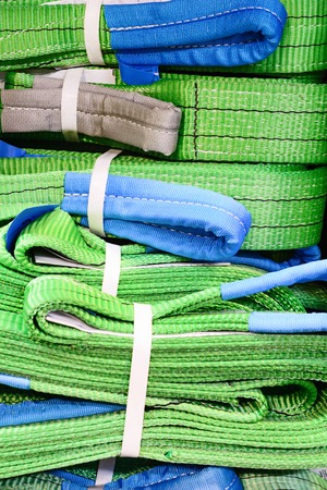 cable stitch: Green nylon soft lifting slings stacked in piles. Warehouse of finished products for industrial enterprises