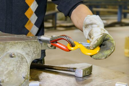 Work sets the load hook into the loop of the steel sling. Manufacture of lifting devices.
