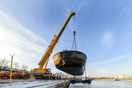 MOSCOW, RUSSIA - NOVEMBER 11, 2016: State Unitary Enterprise Mosvodostok performs recovery vessels on coastal winter parking. River barge lifted truck crane.. Editorial