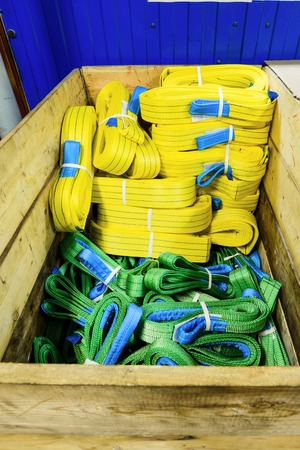 backstitch: Nylon soft lifting slings stacked in a wooden box. Warehouse of finished products for industrial enterprises