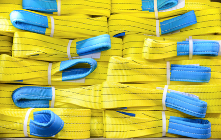 cable stitch: Yellow nylon soft lifting slings stacked in piles. Warehouse of finished products for industrial enterprises