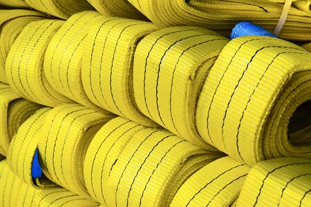 Yellow nylon soft lifting slings stacked in piles. Warehouse of finished products for industrial enterprises