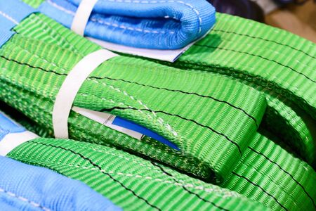 Green nylon soft lifting slings stacked in piles. Warehouse of finished products for industrial enterprises