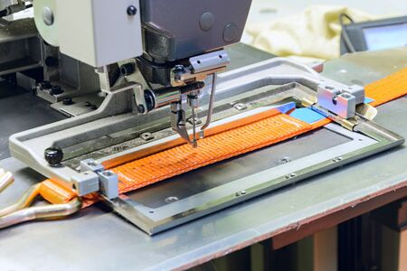 duty belt: Industrial sewing machine sews a ratchet strap. Manufacture of textile slings and tie straps.