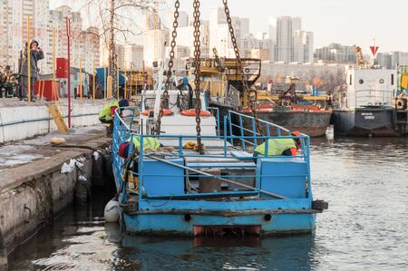 MOSCOW, RUSSIA - NOVEMBER 11, 2016: State Unitary Enterprise Mosvodostok performs recovery vessels on coastal winter parking. Two workers unhooks the load hook. Editorial