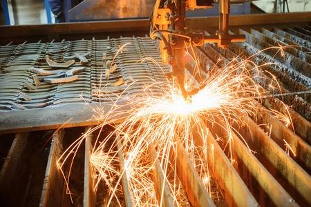 Oxygen torch cuts steel sheet. CNC gas cutting machine. Bright sheaf of sparks of molten metal Stock Photo