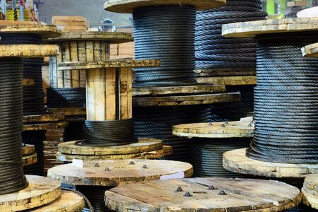 Large cable reels stocked in the factory premises. Workshop production of cable slings. Stock Photo