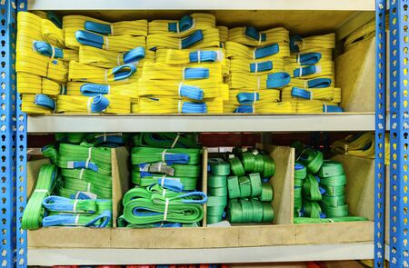 cable stitch: Green, yellow nylon soft lifting slings stacked in piles. Warehouse of finished products for industrial enterprises