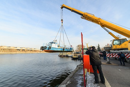 MOSCOW, RUSSIA - NOVEMBER 11, 2016: State Unitary Enterprise Mosvodostok performs recovery vessels on coastal winter parking. Videographer photographs work truck crane. Editorial