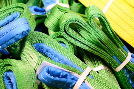 backstitch: Green nylon soft lifting slings stacked in piles. Warehouse of finished products for industrial enterprises