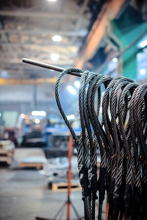 Many steel wire rope sling hanging vertically on a shelf. Finished goods warehouse.